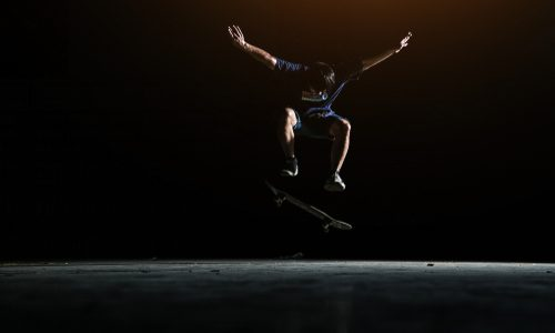 Person performs trick on a skateboard in front of a black background.